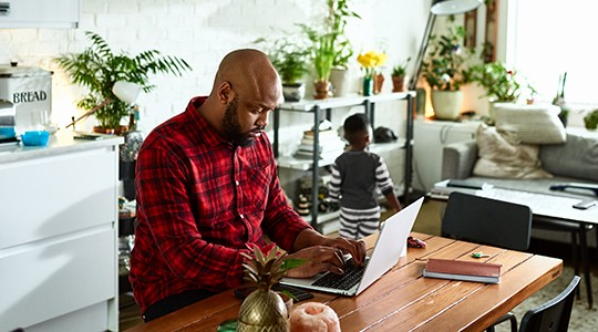 man working from home on a laptop surrounded by house plants with his son playing in the background