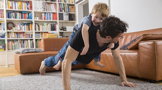 man doing push ups with his son on laughing on his back in the living room