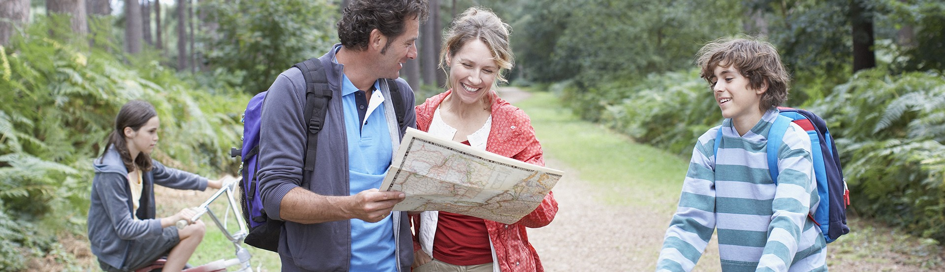 mother and father smiling and reading a map in the woods with their kids on bikes around them