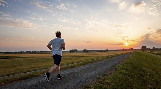 man running down a dirt road among a flat landscape into the sunset