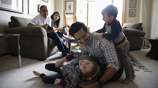 man playing with two kids on the floor of a living room with a woman and older man on the couch behind them