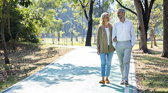 older couple walking and talking in a sunny park