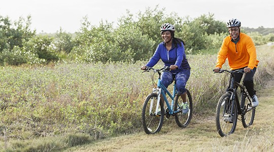 man and woman smiling and biking through a field