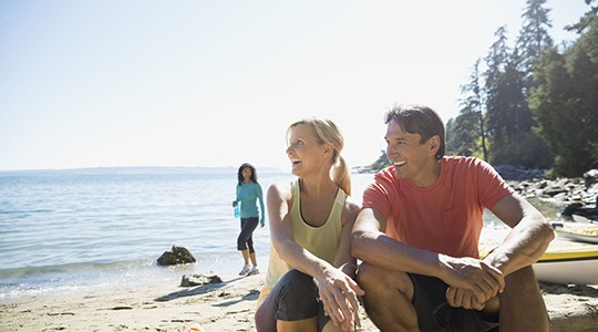 man and woman on the beach in activewear smiling and looking out at the water with a woman in the background