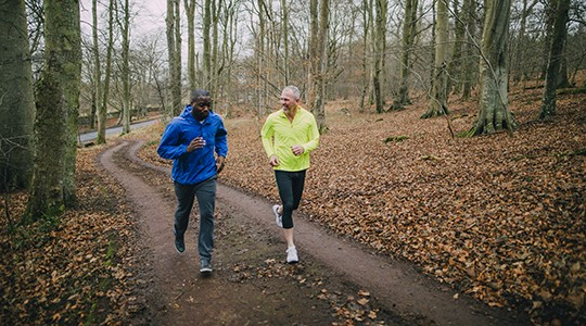 two older men jogging a dirt path in the woods during fall