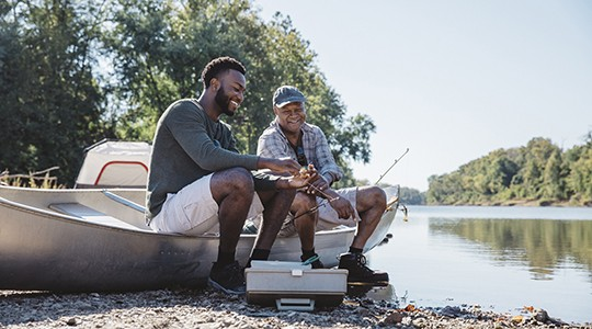 man and older man sitting on a boat and setting up their fishing gear at the edge of a lake