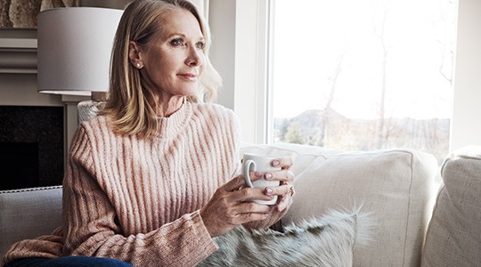 older woman in a turtle neck sitting on a couch with a cup of coffee looking out a window